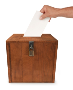 A man's hand putting an envelope in the slot of a box