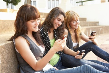 Group Of Teenage Students Sitting Outside On College Steps Using Mobile Phone