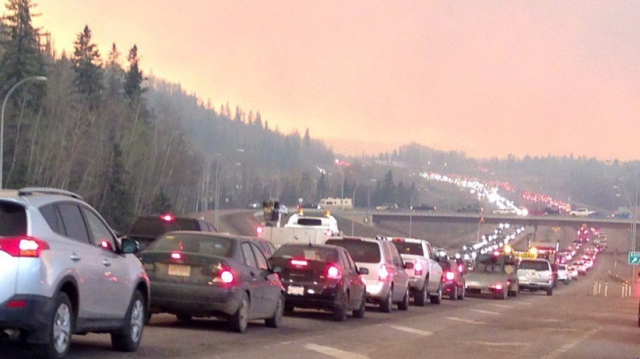 Smoke fills the air as cars line up on a road in Fort McMurray, Alberta on Tuesday May 3, 2016 in this image provide by radio station CAOS91.1. At least half of the city of Fort McMurray in northern Alberta was under an evacuation notice Tuesday as a wildfire whipped by winds engulfed homes and sent ash raining down on residents. (CP)